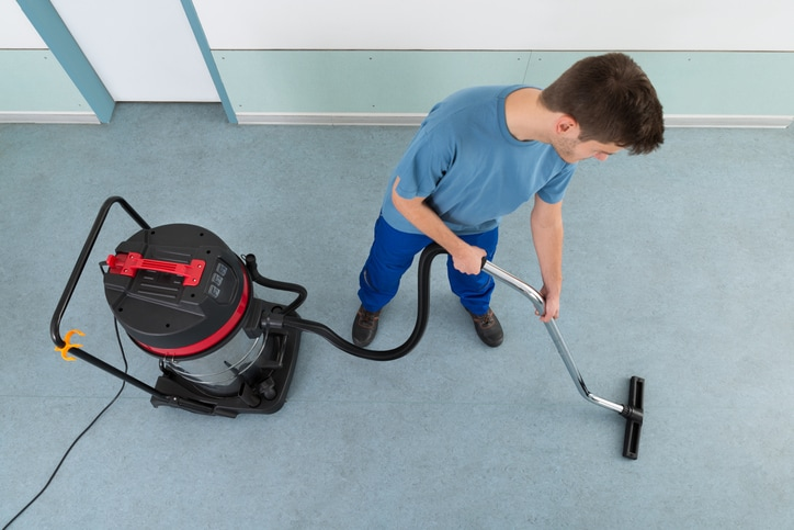 Young Happy Male Worker Cleaning Floor With Vacuum Cleaner
